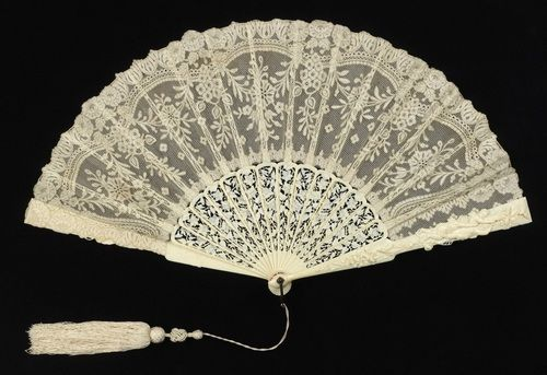 Pleated fan, 1885-1890. Leaf of cotton bobbin-made lace backed with silk; sticks of pierced and carved ivory; metal loop at the rivet. Attached tassel.Courtesy of the Cooper-Hewitt National Design Museum.
