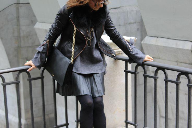 Vestida de gris y negro, cazadora de piel, cuello de pelo negro, falda de piel, medias negras, bolso negro, jersey de punto.melena mido.