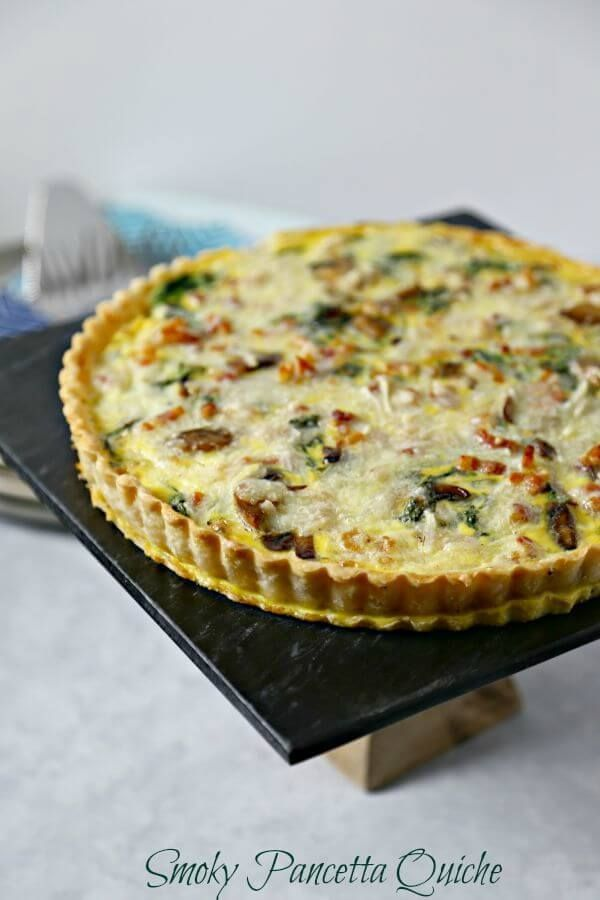 This Smoky Pancetta Quiche from CookingInStilettos.com is perfect for brunch, lunch or even dinner. Crisp pancetta, fresh arugula and buttery mushrooms are baked in a cheesy egg custard that will have your guests swooning with every bite.