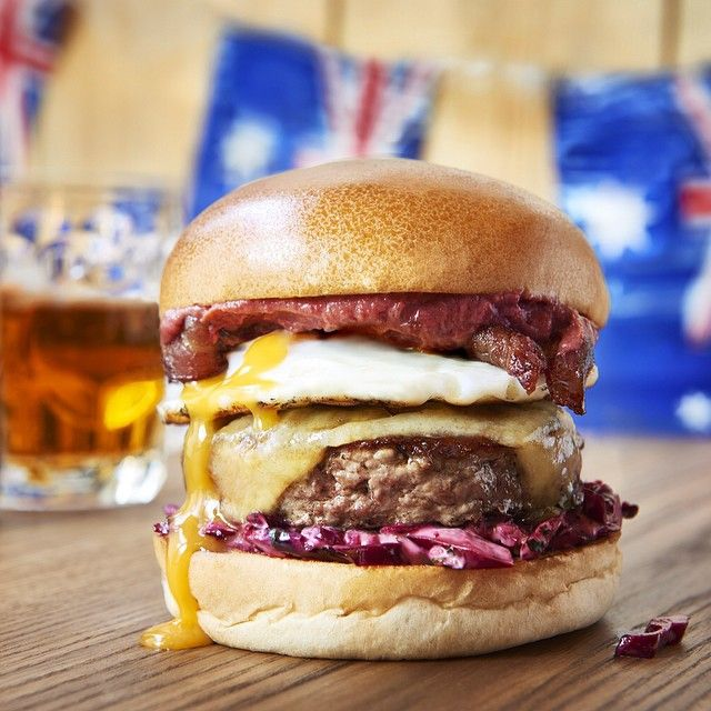 """The """"Australian"""" burger. Aged Wagyu beef patty, smoked bacon, beetroot guacamole, fried egg, cheddar and apple coleslaw on a glossy brioche bun."""