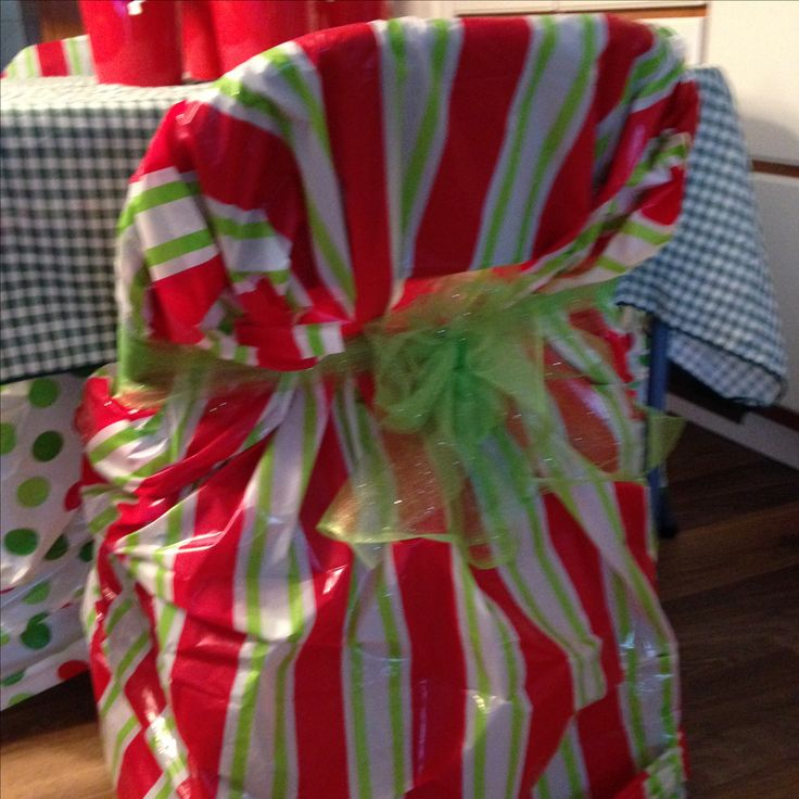 Festive kids' table chair cover - dollar store plastic gift bag & a sparkly green tulle bow!