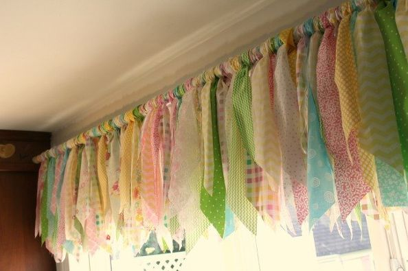 Kitchen window treatment using a tension rod and strips of fabric tied to it. Really cute