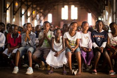 Rwandan children listen and pray during a Sunday morning service at the Saint-Famille Catholic church, the scene of many killings during the 1994 genocide, in the capital Kigali, Rwanda Sunday, April 6, 2014. (AP Photo/Ben Curtis) Photography