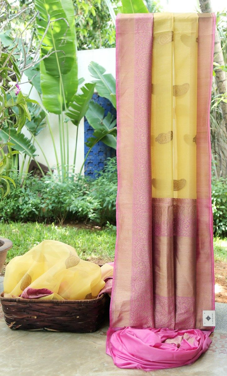 This yellow Benares kora has gold zari bhuttas placed at regular intervals. The contrasting pallu and border are in pink with intricately woven gold zari giving a beautiful sheen to this light sari