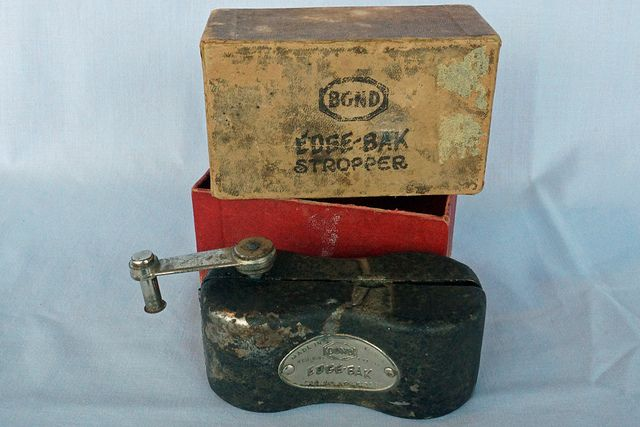 "This is an early hand cranked razor stropper by Bond Electric Corporation. This looks like it may have been made in the 1930's. It is in good condition and comes in its original box. Once the blade is mounted the little stroppers rub across the edge to sharpen. It measures 4"" long x 1 3/4"" x 1 3/4"". Nice vintage item!  Tin Can Alley    inside the Castle Rock Mercantile Antique Mall  160 H Huntington Avenue N  Castle Rock, WA 98611 www.bagtheweb.com/b/UG8KRi bagtheweb.com/b/E7Kxc0"