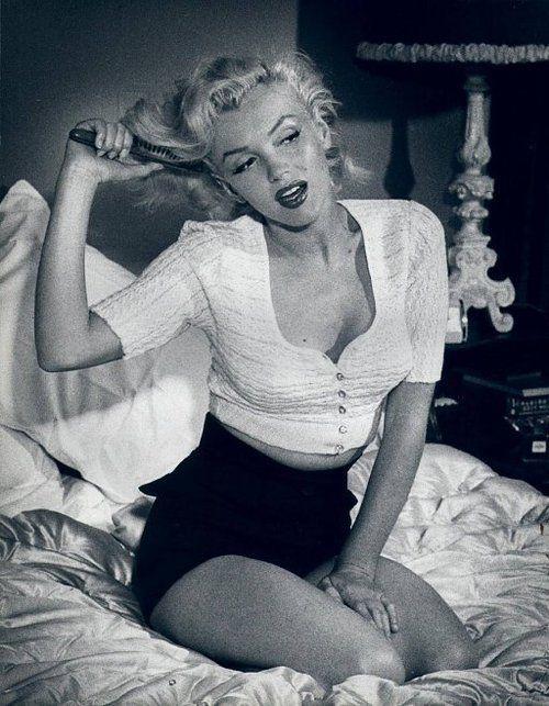 Marilyn Monroe brushing her hair.