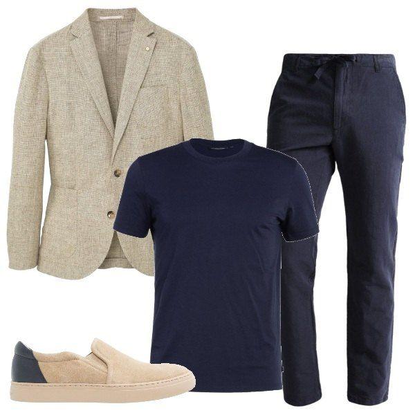 Il lino è il tessuto che caratterizza questa proposta che si compone di una giacca beige, da indossare sopra una t- shirt blu come i pantaloni. Le scarpe sono delle slip on bicolore, che richiamano entrambi i colori della proposta.