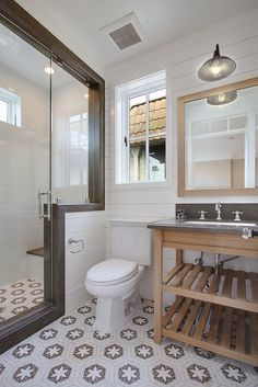 Interesting Tile, Metal framed glass shower, Wall Planks, Natural Wood mirror and vanity, Industrial light