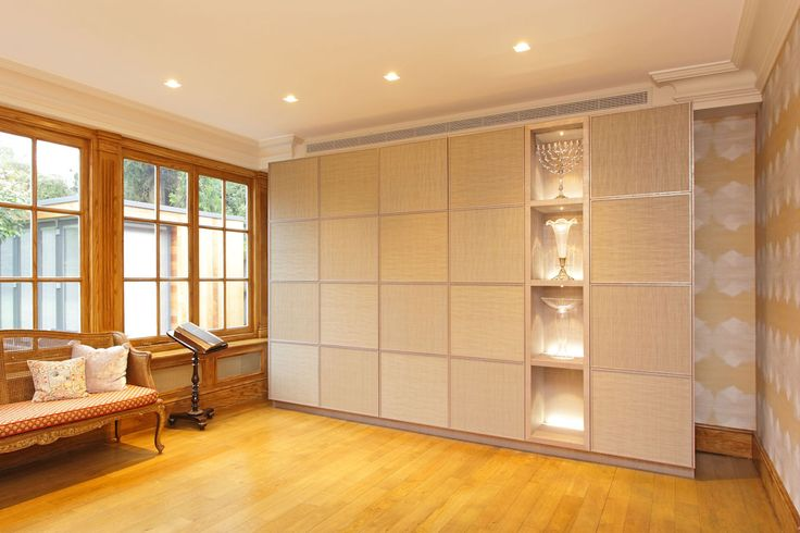 This cabinet was designed and made for a whisky connoisseur and has a section featuring a serving area which is illuminated. The doors have mirrored backs to add to the ambience. The cabinet doors are covered in 'metallic' wallpapers. By Andrew Manning Furniture