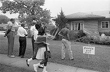 "A black and white photograph of a suburban house with minor bomb damage to the roof and two windows while five black Birmingham residents stare at the damage; the yard is cordoned off with a sign saying ""Danger Keep Out"""