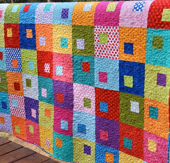 Spring is here and this Handmade quilt will show off all the bright and colorful shades that accompany it! Vibrant and bold colors of the rainbow make up this fun quilt. Some fabrics are from the This n That collection by Nancy Halvorsen, others are matching solids, others are fun dots and a few stripes......all make a gorgeous, colorful quilt.    The quilt measures 42 x 53...this is wonderful for a crib, on the floor for playtime, tossed across a chair, or on your lap for snuggling…