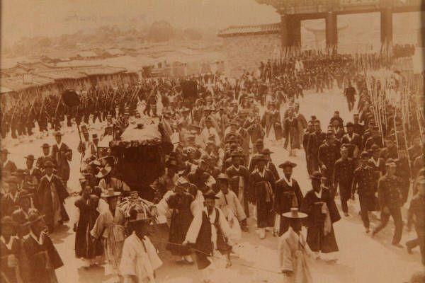 경운궁 대안문을 나서는 명성황후 장례 행렬. 사진 뒤에 '황후의 운구 장면'이라고 적혀 있다.