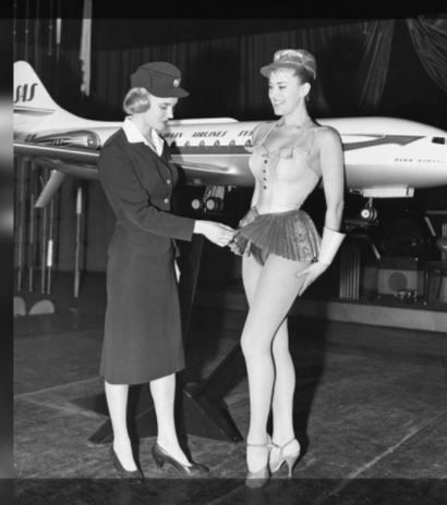 A 1959 photo of a Scandinavian Airlines employee checking the skirt length of stewardess' uniform. SAS Airlines Uniform Check.