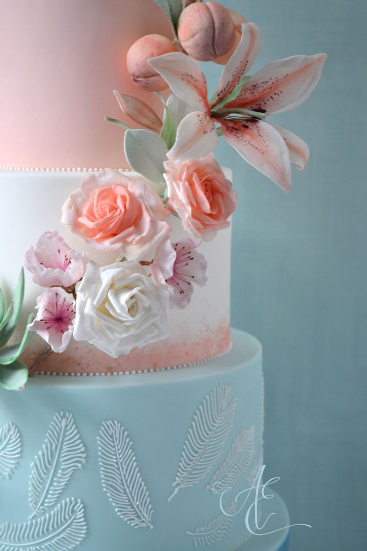 Wedding cake iced in pastel mint, peach and white with watercolour and gold accents, and a cascade of sugar florals, fruit and foliage. The sugar and hand piped feathers are inspired by Falcon Manor's beautiful light fittings!