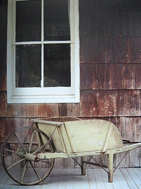 Old Green Wood Wheelbarrow...on a weathered porch.