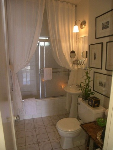 small bathroom made fancy with floor to ceiling curtains in front of shower doors.