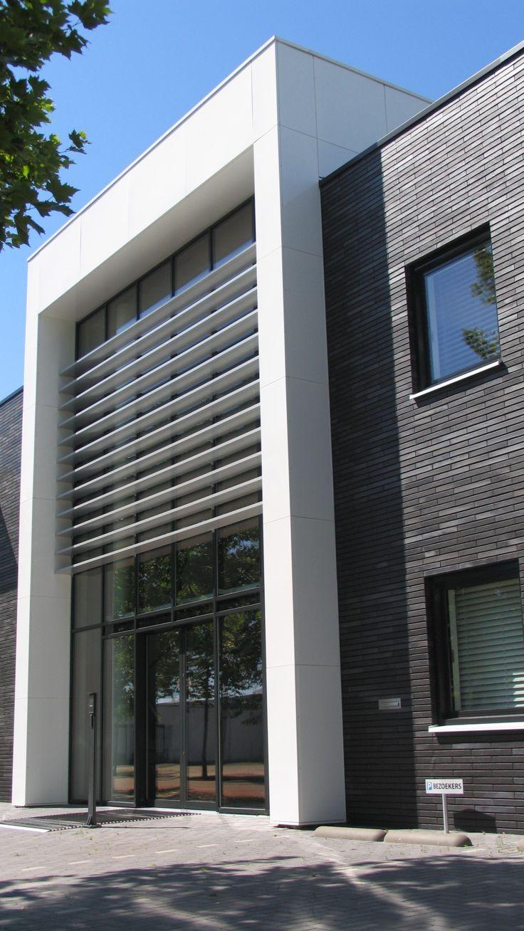 bedrijfsgebouw PK Benelux in donker metselwerk met een witte kadrering ter plaatse van entree en hoekraam