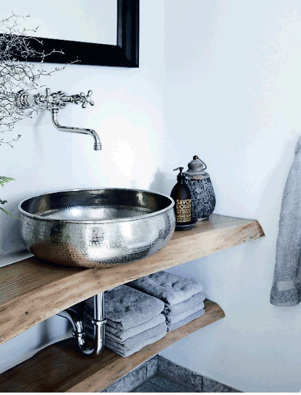 SIlver wash basin placed on the top of the wooden shelf. Rustique looking bathroom with a touch of luxury. we love it!