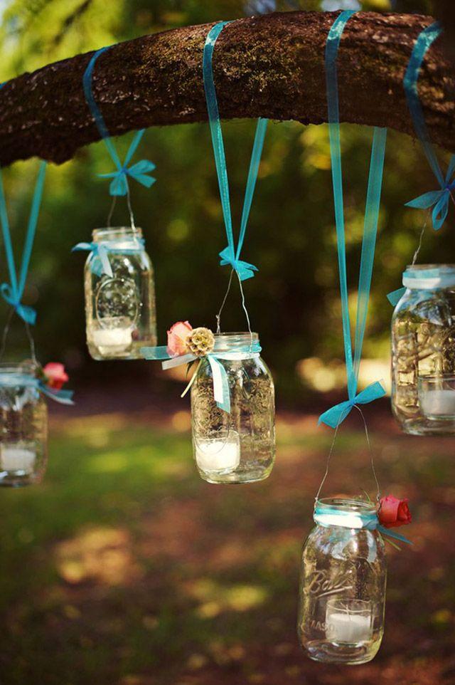 Frascos conserveros de vidrio transparente colgando desde la rama de un árbol con cinta calipso y cada frasco con una vela dentro.