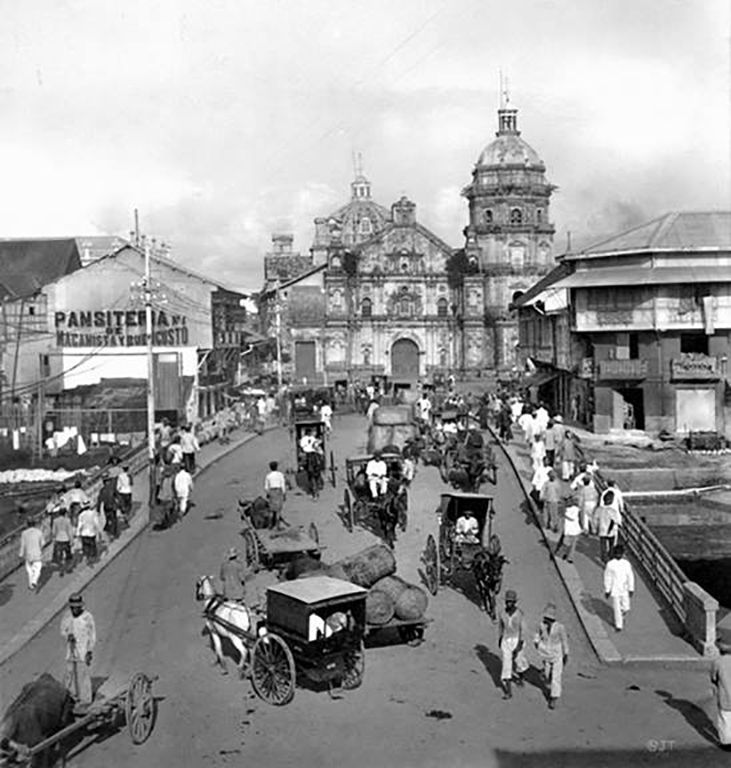 """020816_Early 1900s photo of Binondo, the world's oldest Chinatown, established in 1594. Binondo Church (aka Minor Basilica of Saint Lorenzo Ruiz and Our Lady of the Most Holy Rosary Parish) is viewed across Binondo Bridge. Also viewed here is a building that housed Panciteria Macanista De Buen Gusto, a restaurant mentioned in chapter 25 of Jose Rizal's """"El Filibusterismo"""".  Photo source: https://www.flickr.com/photos/johntewell/5823501089 ... More: https://en.wikipedia.org/wiki/Binondo ."""