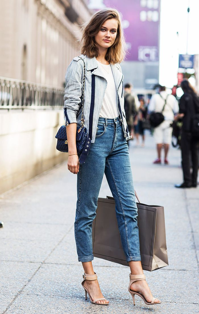 "Monika ""Jac"" Jagaciak in a pair of high waisted jeans, a moto jacket, white t-shirt, and strappy nude heels"