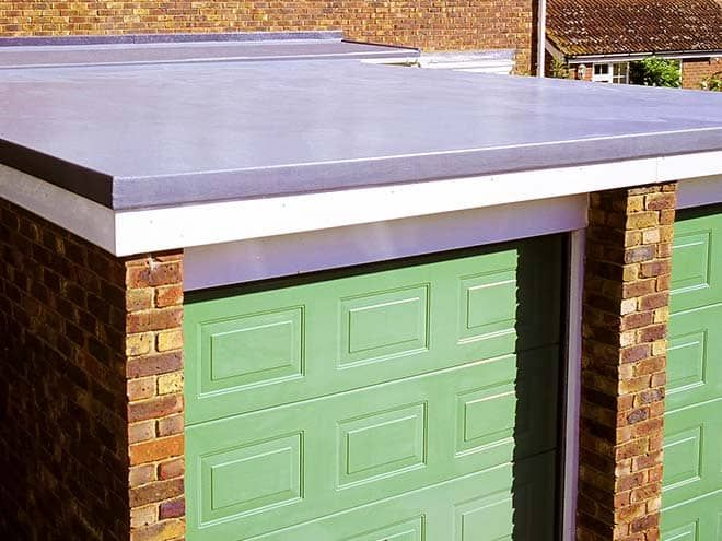 Angled view of an Everest Flat Roof atop a garage with a green door