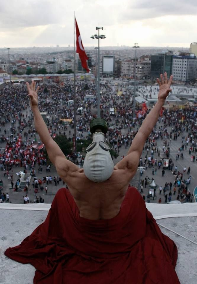 A man wearing a gas mask on top of Ataturk Cultural Center, Taksim