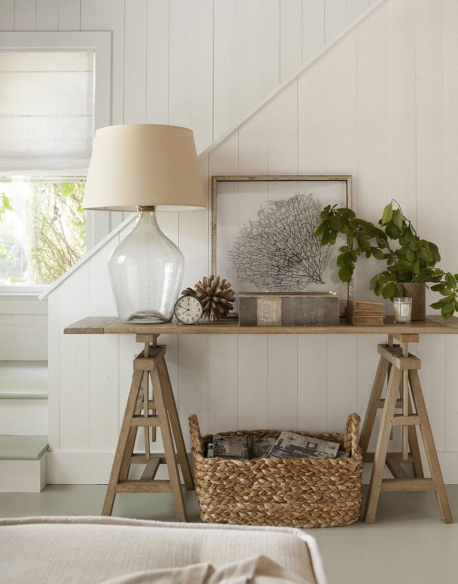 This neutral foyer is decorated with a large seagrass basket tucked under a wood sawhorse table, topped with glass lamp, framed sea fan and natural plant