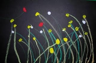 Tapa de primavera:cartolina negre, troncs amb xocs i flors amb tempera de dits