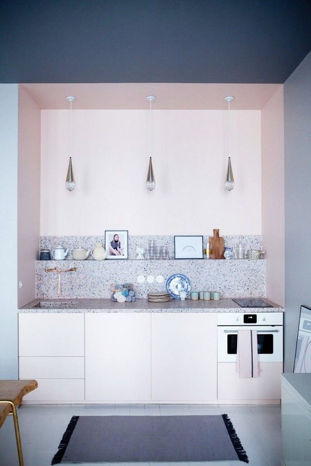 Kitchen with a cut-in, pink cabinents, and modern sconce