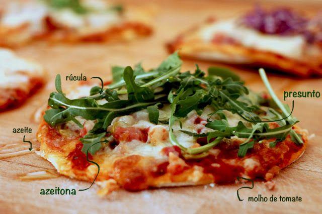Pizza de presunto e azeitonas  Ingredientes:  Presunto aos cubos Azeitonas sem caroços recheadas com pimento Queijo de cabra ralado Azeite extra-virgem q.b. Rúcula