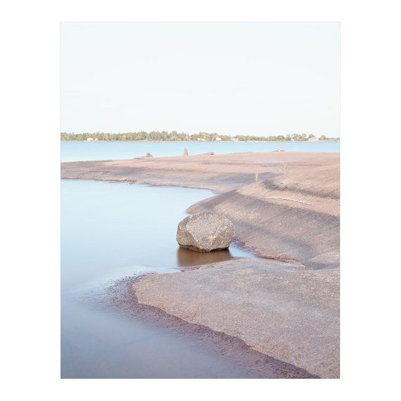 Canadian landscape photography of the calm Lake Huron water surrounding outcroppings of pink Muskoka Canadian Shield on a warm summer day.