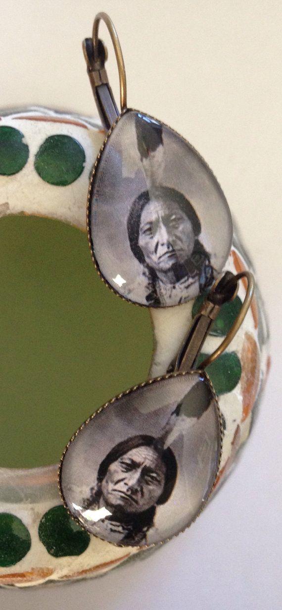 Boucles d'oreilles de type dormeuses, en métal de couleur bronze, serties d'un cabochon bombé en verre, en forme de goutte, mesurant 25 mm x 18 mm. Dimensions des boucles d'oreilles : 37 mm x 19 mm. Photographie datant de 1885, représentant le chef indien Sitting Bull (≈1831-1890). Sitting Bull est né vers 1831 dans le Dakota du Sud et mort le 15 décembre 1890 dans la réserve indienne de Standing Rock. Photographie © Maní