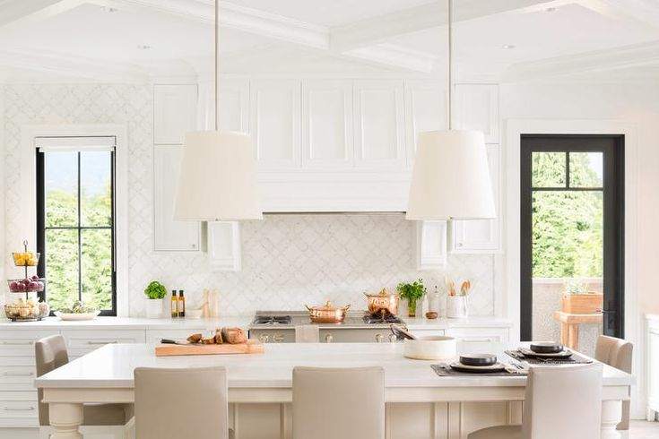 Bright, airy kitchen features two tapered drum pendant lights illuminating an ivory center island fitted with ivory turned legs and lined with light gray upholstered counter stools.