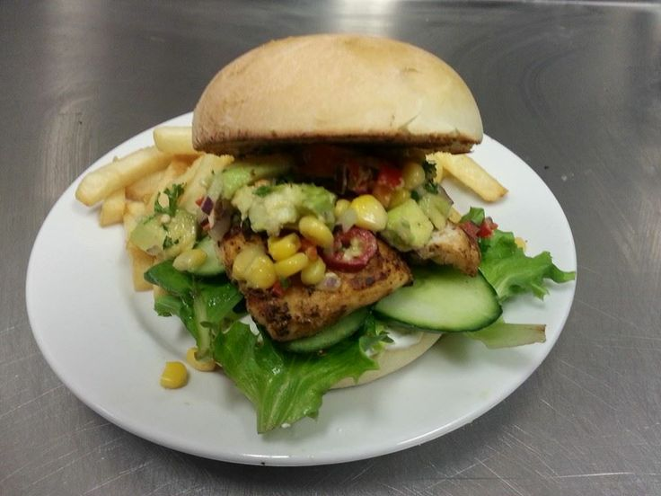 cajun chicken burger with avocado and chilli salsa, mint yoghurt, cucumber and lettuce.