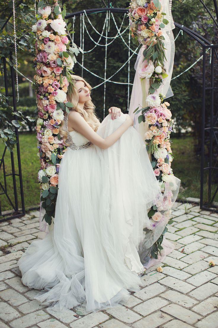 Bride on floral garden swing. Woodland garden wedding. Wedding photo