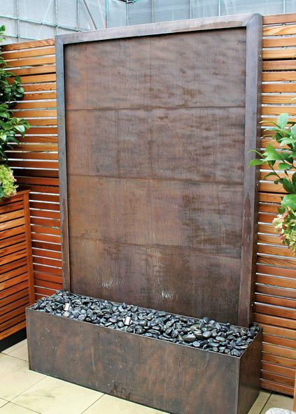 Antiqued copper panels and a copper frame create an unusual surface for water to run down.