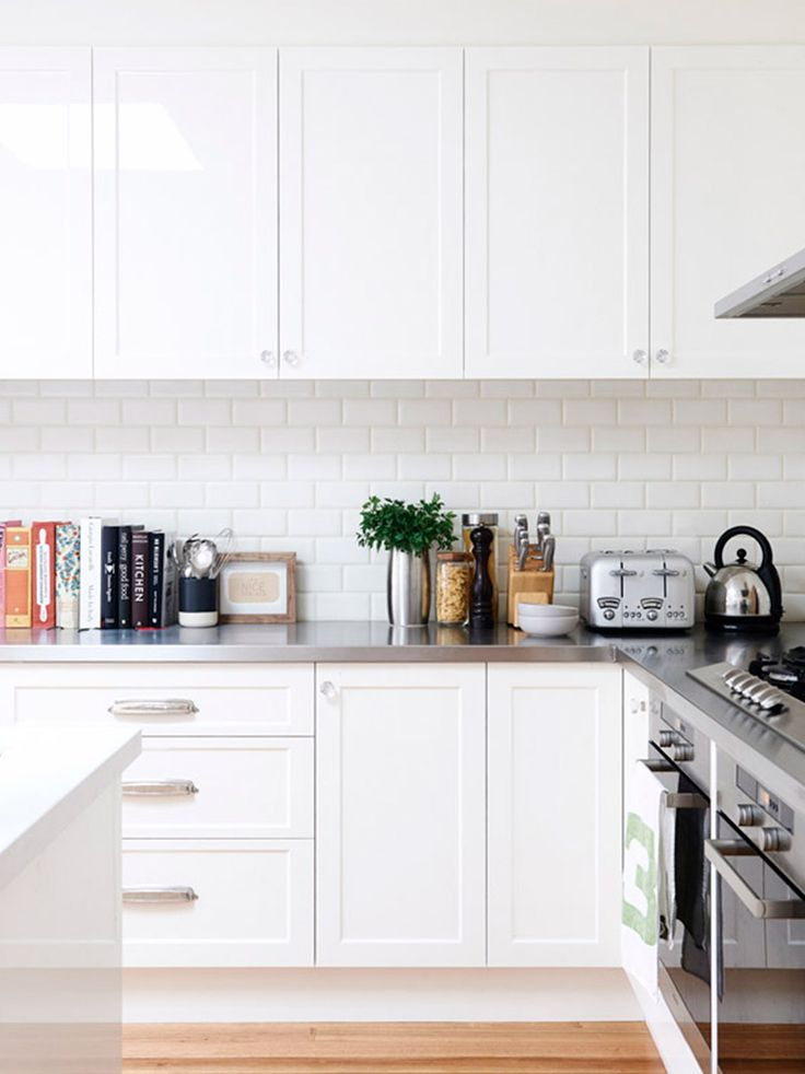 White kitchen with marble countertop and stainless steel appliances