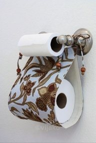 Tie a swath of decorative fabric below toilet paper holders for a pretty and convenient storage solution. #DIY #bathroom #storage