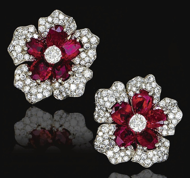 PAIR OF RUBY AND DIAMOND EAR CLIPS, VAN CLEEF & ARPELS, 1952.  Each designed as a flower head, set with oval rubies and brilliant-cut diamonds, mounted in platinum.