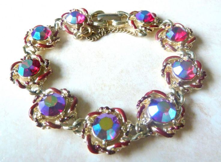 A Vintage aurora borealis rhinestone studded bracelet by Jewelcraft The bracelet is formed from gold tone metal set in nine small circular panels