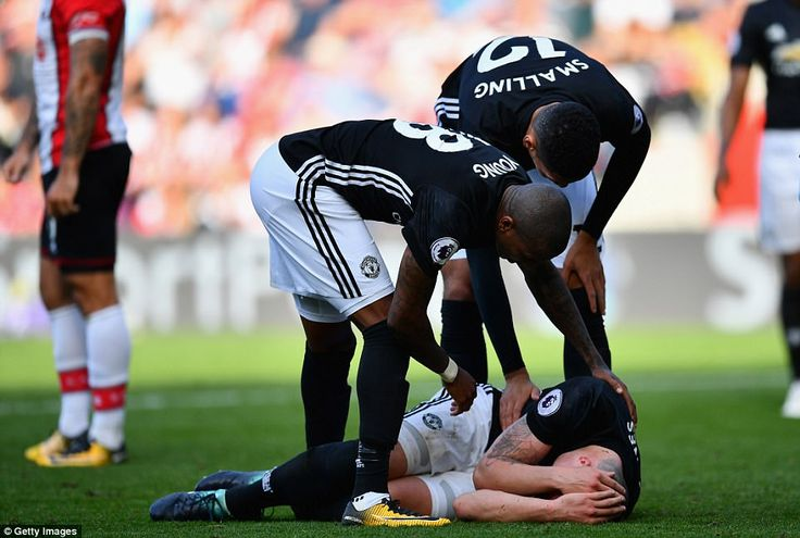 Phil Jones goes down with a head injury while Ashley Young and Chris Smalling check to see if their team-mate is alright