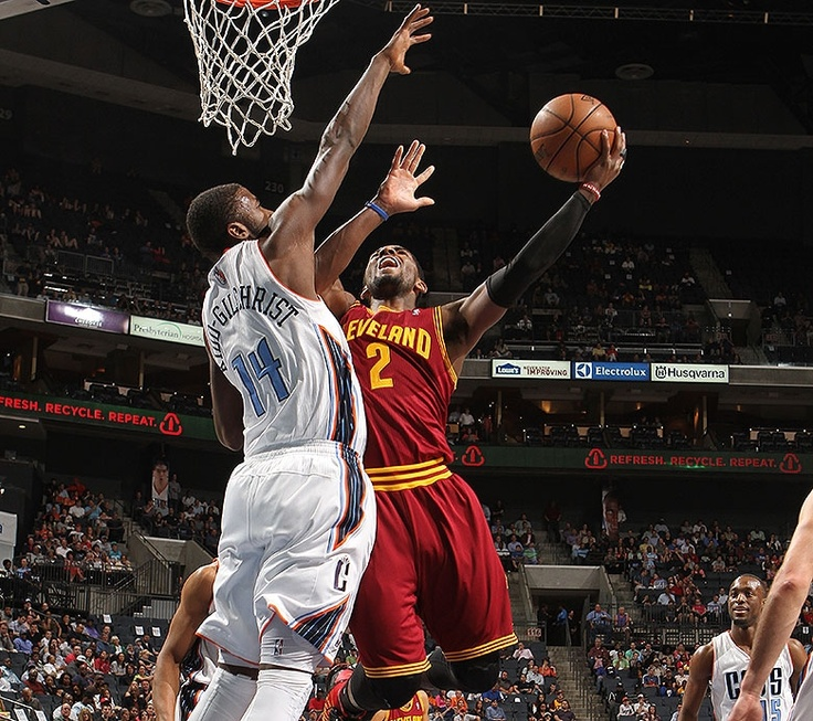 Guard Kyrie Irving puts up the acrobatic shot against Michael Kidd-Gilchrist of the Charlotte Bobcats at The Time Warner Cable Arena in Charlotte, North Carolina - photo courtesy of Kent Smith / NBAE via Getty Images.