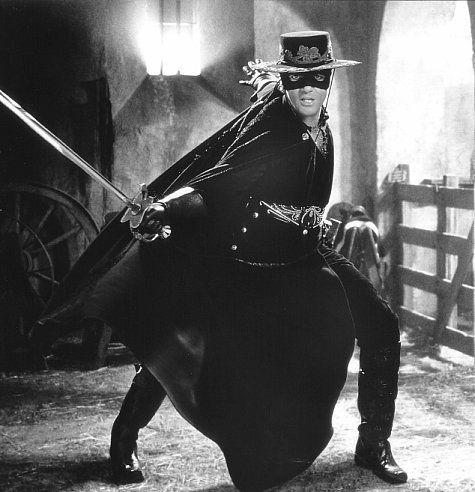 Se llama Antonio Banderas. Él es de Benalmádena, España. Lleva un sombrero negro con oro, unas botas negros, un cinturón negro, una camisa negra de oro, unos guantes negros, unos pantalones negros.