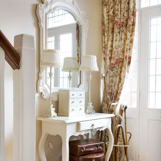 Small hallway with white dressing table, white ornate mirror and neutral floral curtain