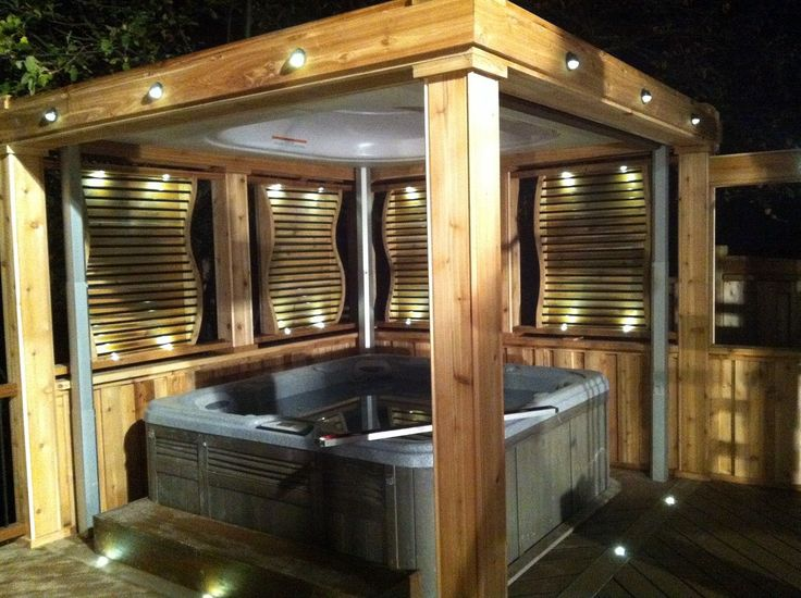 """Enclosed hot tub area complete with lighting, privacy screens and curtains.  The roof is also a retractable cover, that lowers onto the tub when not in use.  From """"Decked Out"""" project """"The Spiral Staircase Deck"""".  Deck Design by Paul Lafrance Design."""