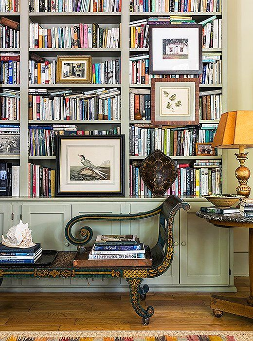 Multiple works of custom framed art hung ON multiple shelves in the library of an obvious bibliophile. A fantastic way to work art into any area of the home!
