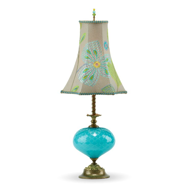 Chelsea by Susan Kinzig and Caryn Kinzig. Chelsea is a whimsical lamp with bright blue blown glass matched with an embroidered linen shade that has a blue and lime green floral design. It has copper coiled around the brass pole of the lamp. Chelsea has a single bulb socket and is adorned with a beaded finial.