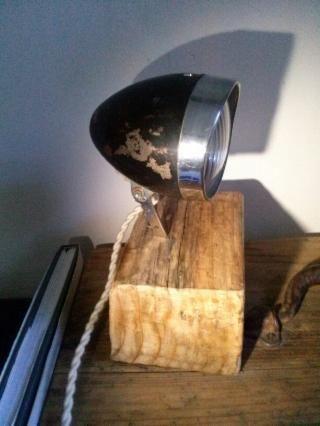 Lámpara de mesa, hecha con un antiguo faro de bici antigua de la marca Mondial. Pie de hierro y base de madera. Cable trenzado blanco a l'estilo antiguo. 60€