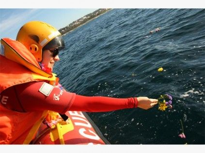 Bianca van Zyl from NSRI throws flowers into the ocean at the Paddle Out for Sharks.